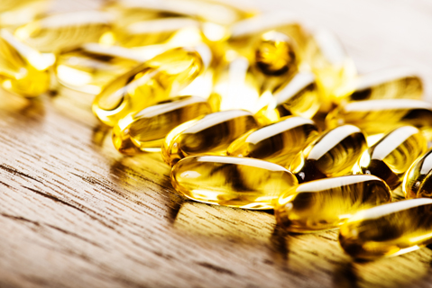 Fish oil capsules isolated on wooden background